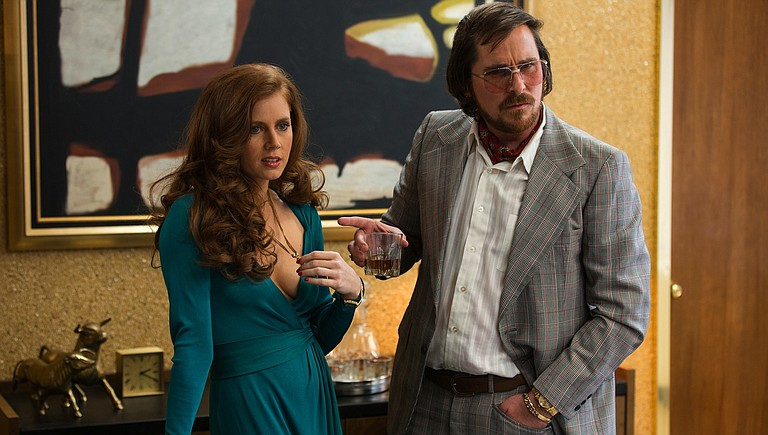 "Sydney Prosser (Amy Adams) and Irving Rosenfeld (Christian Bale) make a cunningly irresistible pair in ""American Hustle."""