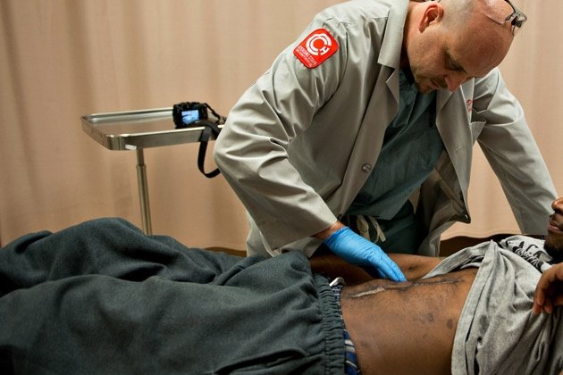 Dr. Andrew Dennis, a surgeon in the Cook County hospital trauma unit, looks at the wound of a man who was shot in 2012 in Chicago, on May 16, 2013. Americans in violent neighborhoods are developing PTSD at rates similar to combat veterans.