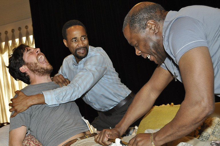 """At rehearsals for New Stage Theatre's production of the """"The Whipping Man,"""" Yohance Myles' character John holds Brian Maxsween's character, Caleb, back as Simon, played by Jay Unger, dresses Caleb's wounded leg."""