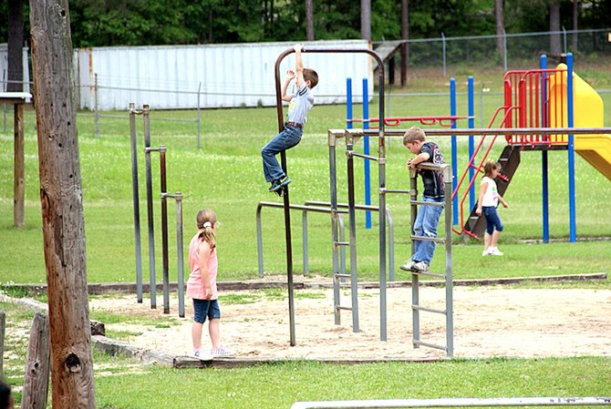 Children in the Richton School District, about 20 miles east of Hattiesburg, play on outdated playground equipment. Across Mississippi, educators say that years of underfunding have left them with inadequate facilities and few supplies.