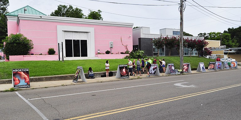 The police stood near Jackson Women's Health Organization, the last abortion clinic in Mississippi, on July 17 as Mike Peters picked up each of the large portable signs and took them to his building's basement./File Photo
