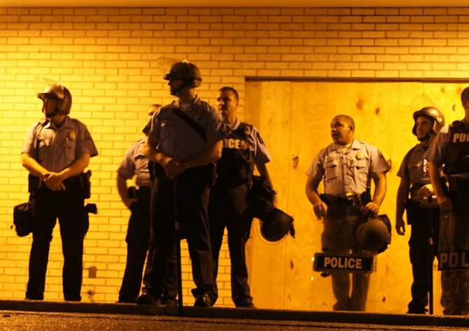 Members of the St. Louis Police Department stand by on the first night of a a curfew that Missouri Gov. Jay Nixon ordered.  Approximately 15 law-enforcement agencies were called to assist during protests.