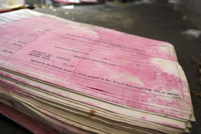Pages of history have turned pink after water damage caused the red cover to bleed onto the book's pages.