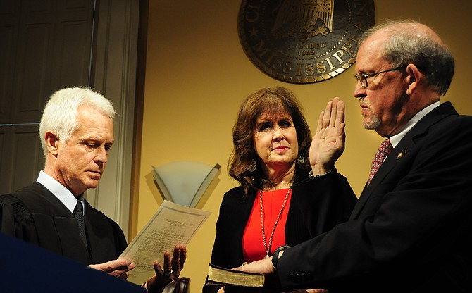 Ashby Foote (right) with his wife, Suzie Foote (center), taking the oath from Hinds County Chancery Judge Bill Singletary (left).