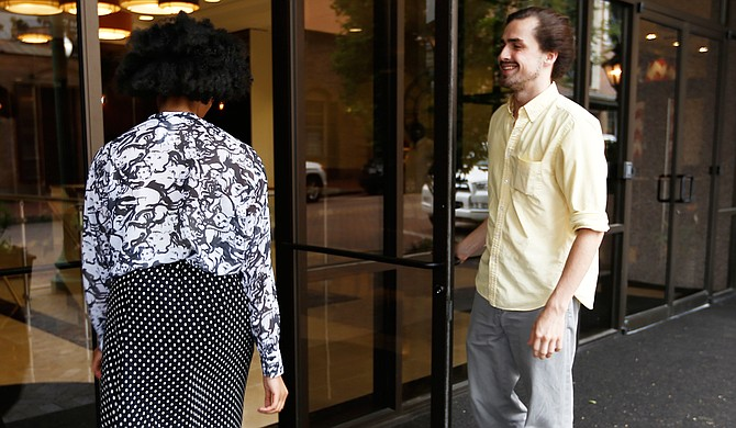 News intern Zachary Oren Smith (right) opens a door for Editorial Assistant Adria Walker (left).
