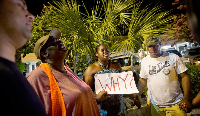 Surreace Cox, of North Charleston, S.C., holds a sign during a prayer vigil down the street from the Emanuel AME Church early Thursday, June 18, 2015, following a shooting Wednesday night in Charleston, S.C. Photo courtesy Associated Press/David Goldman