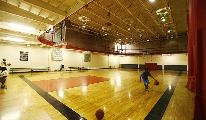 A young man shoots a basketball on a recent day at the downtown Jackson YMCA. The courts will soon be gone.