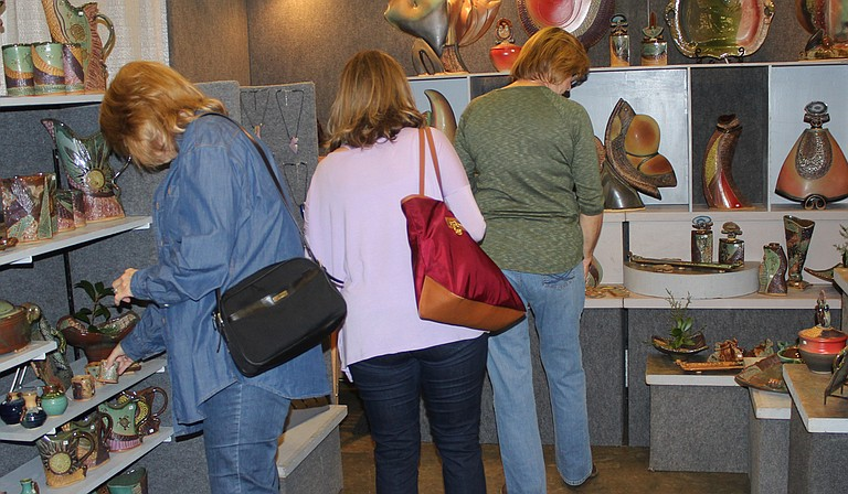 Chimneyville Craft Festival attendees browse the pottery in artist Helene Fielder's booth at the event. Photo courtesy Craftsmen Guild of Mississippi