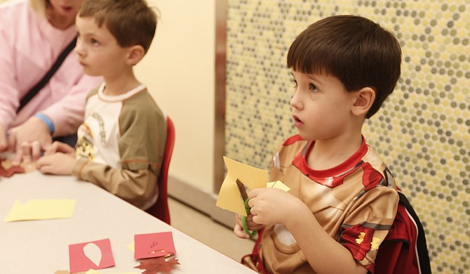 """Owen Williamson (left) and Caleb Hinton (right) create paper turkeys on Nov. 25 at the """"ABC, Come Play with Me"""" workshop at the Mississippi Children's Museum."""