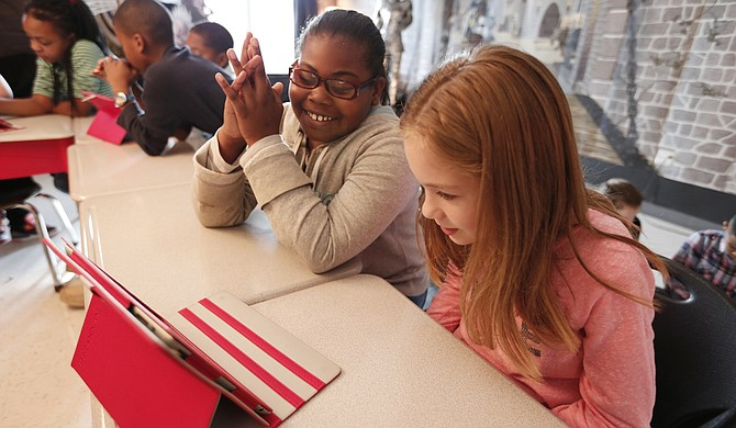 Quintaria Wright (left) and Avery Berg (right) work on a coding app called Lightbot during Eastside Elementary's Hour of Code on Dec. 9.