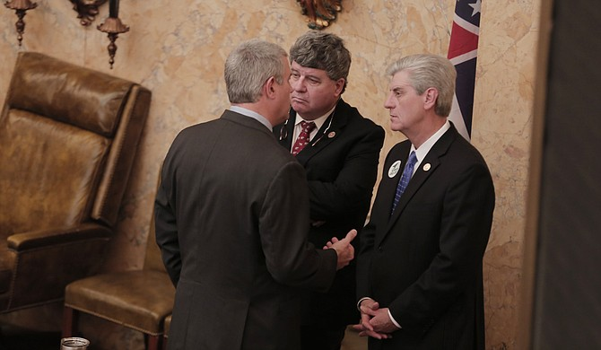 Gov. Phil Bryant (right) speaks with Speaker Philip Gunn (left), R-Clinton, and Speaker Pro Tem Greg Snowden (center), R-Meridian, after the dual-project bill passed through the House.