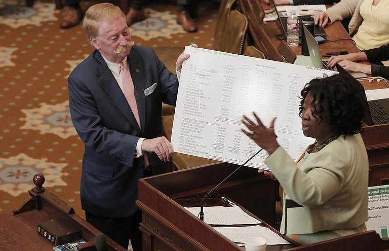 Rep. Jeff Smith, R-Columbus, (left) helps Rep. Omeria Scott, D-Laurel, show her poster boards displaying income-tax revenue numbers as she spoke on the Taxpayer Pay Raise Act on Monday in the House.