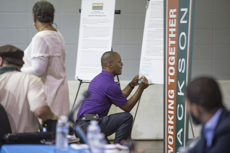 Ward 4 Councilman De'Keither Stamps signs the accountability board at the Working Together Jackson assembly Emmanuel Missionary Baptist Church in south Jackson. Stamps is unopposed for the June 6 general election.