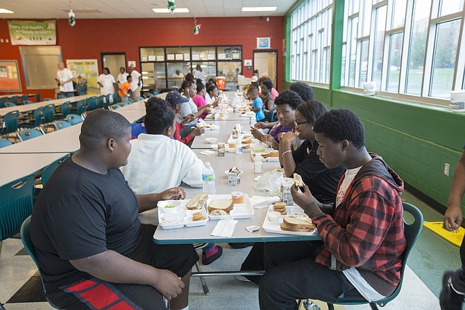 Children eat lunch at Blackburn Elementary School on June 23. The JPS Food Service Program provides the children with free meals.