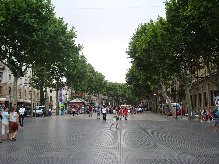 Las Ramblas, a street of stalls and shops that cuts through the center of Barcelona, is one of the city's top tourist destinations. People walk down a wide, pedestrian path in the center of the street but cars can travel on either side. Photo courtesy Flickr/Juan Pablo Ortiz Arechiga