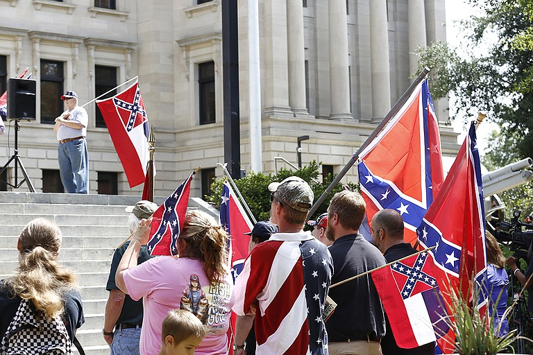 Mississippians supporting the state flag rallied outside the Capitol a month after Dylann Roof, a white supremacist, murdered nine African Americans in South Carolina. Investigators found pictures of him holding a rebel flag.