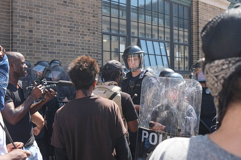 Hundreds of riot police mobilized downtown late Sunday, arresting more than 80 people and seizing weapons amid reports of property damage and vandalism. The arrests came after demonstrators ignored orders to disperse, police said. Photo courtesy Flickr/Paul Sableman