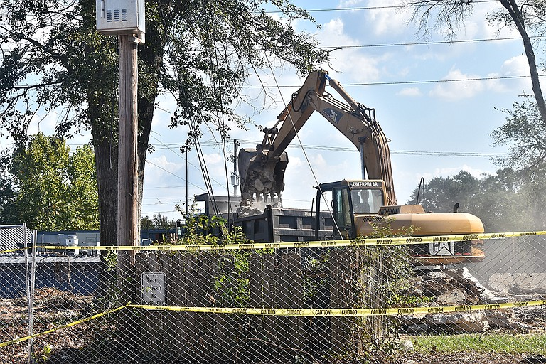"""Construction workers clean the debris and remains from the """"Fondren House"""" on North State Street that developers demolished on Sept. 21."""