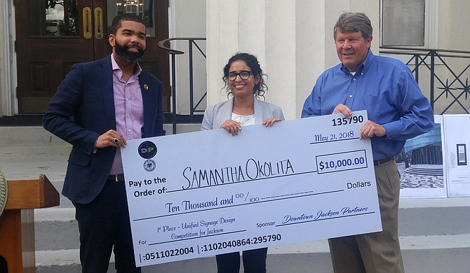 Mayor Chokwe Antar Lumumba presents a check to Salam Rida, Urban Designer with the City of Jackson's Long-Range Planning Division, who is accepting on behalf of Samantha Okolita of Brooklyn, N.Y. Okolita won the Unified Signage Competition. On the right is Ben Allen, president of Downtown Jackson Partners.