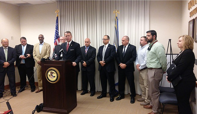 A federally organized drug task force arrested 11 people near Philadelphia, Miss., on May 30, U.S. Attorney Mike Hurst said at a press conference. Law enforcement personnel are standing behind him.