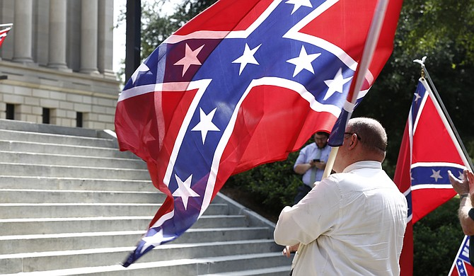 Demonstrators with the Poor People's Campaign burned a Confederate battle flag and then a separate Mississippi state flag Monday in front of the governor's mansion. Mississippi's flag has contained the Confederate battle emblem since 1894, and residents who voted in a 2001 statewide election chose to keep the emblem on it.