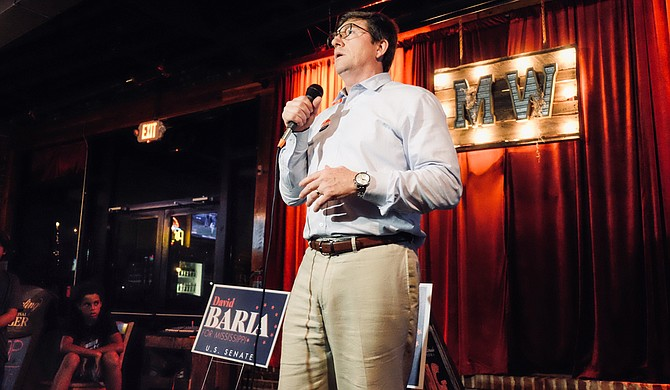 After winning the Democratic primary for U.S. Senate on June 26, 2018, Democrat David Baria speaks to a crowd of supporters in Gulfport, Miss., while his son, Max, 10, watches nearby.