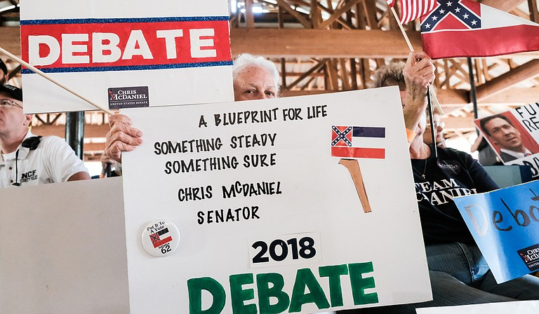 As incumbent Republican U.S. Sen. Cindy Hyde-Smith speaks at the Neshoba County Fair in Philadelphia Miss., on Aug. 2, 2018, supporters of her Republican challenger, Mississippi State Sen. Chris McDaniel, hold up signs calling on her to join him for a debate.