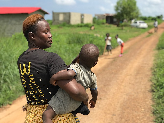 Sianneh Beyan, 32, and her 11-month-old son, Charles Allen, walk down a winding dirt road in Liberia to finish laundry.