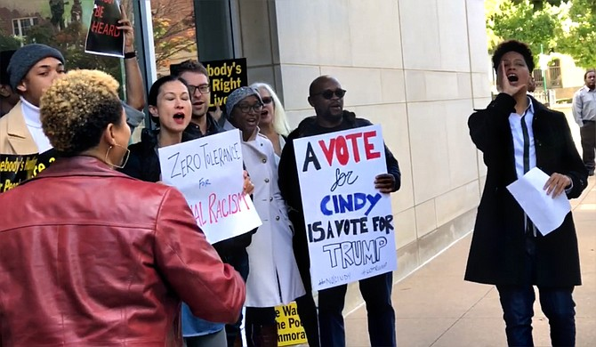 Approximately 30 protesters gathered on the sidewalk on Nov. 16, 2018, outside U.S. Sen. Cindy Hyde-Smith's office, calling for her resignation. Co-organizer Genesis Be, a Gulf Coast native, is pictured to the right. Photo by Ko Bragg