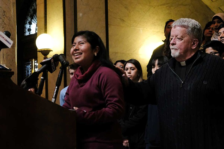 """Mississippi Immigrants Rights Alliance Board of Directors member Father Jerry Tobin puts his hands on Yitzel, a young immigrant, as she sobbed from behind a podium in the Mississippi Capitol on Jan. 30. """"I had to grow up really fast,"""" she said."""