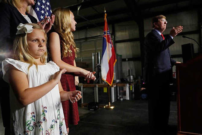 Maddie Reeves, 7, left, the youngest daughter of Lt. Gov. Tate Reeves, applauds during her father's speech during the kickoff event for his race for governor, Monday, April 8, 2019, in Pearl, Miss. Photo by Rogelio V. Solis via AP