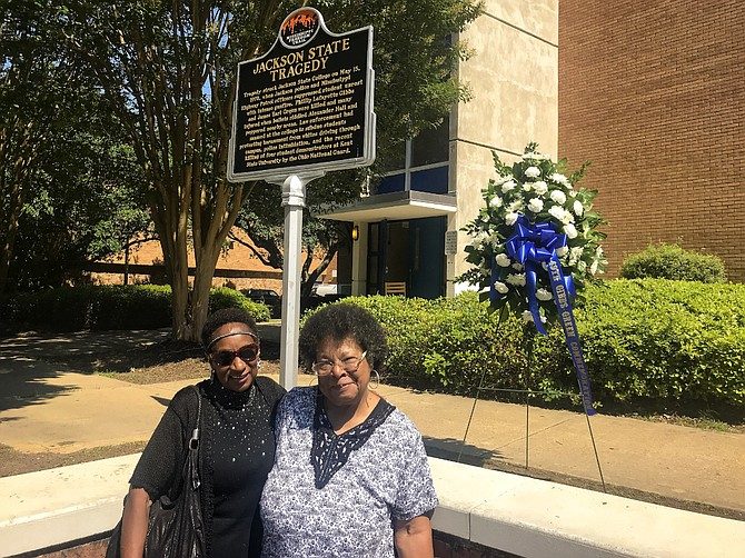 Gloria Green-McCray (right) and Mattie Hull (left) the sisters of James Earl Green, stand beside a marker and wreath outside Alexander Hall on the Jackson State University campus on May 15, 2019 - 49 years after city and state police opened fire on a group of youth, killing their brother and one other. Photo by Aliyah Veal