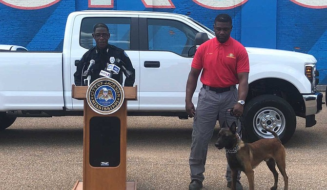 Officer Sam Brown (left) talks about the new bomb squad truck and equipment, while Aaron Allen (right), the canine handler, stands by with the new dog, Loki.