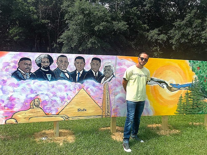 Eli Childers, a local Jackson artist, stands in the middle of the 72-foot mural along the fence of Wilkins Elementary School in south Jackson.