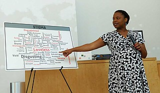 Alecia Reed-Owens, staff attorney for the Mississippi Center for Justice, points to different words that represent the stigma associated with HIV at Refill Cafe's Friday Forum on July 12. Photo by Josh Wright