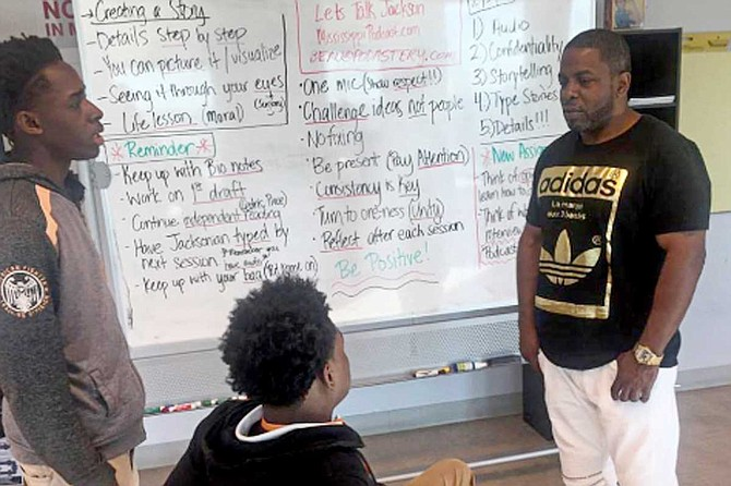 Cedric Willis, who was in prison for 12 years for a murder he didn't commit, talks to Youth Media Project students Dartavious Archie (left) and Marquavious Harris in spring 2017. The students were part of the Wingfield High School FAME program. Photo by Donna Ladd
