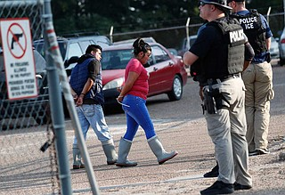 Two people are taken into custody at a Koch Foods Inc. plant in Morton, Miss., on Wednesday, Aug. 7, 2019. U.S. immigration officials raided several Mississippi food processing plants on Wednesday and signaled that the early-morning strikes were part of a large-scale operation targeting owners as well as employees. Photo by Rogelio V. Solis via AP