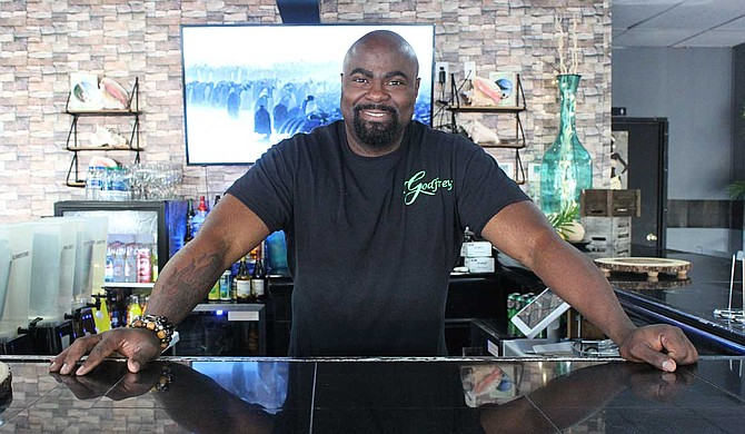 Chef and restaurant owner Godfrey Morgan stands behind the bar of his restaurant, Godfrey's, which serves cuisine from southern, Asian and Caribbean cultures. Photo by Aliyah Veal
