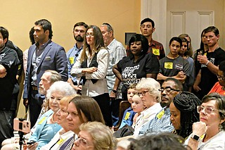"""Fondren resident Scotta Brady, center left, stands with a few abortion-rights supporters amid a crowd of anti-abortion activists wearing yellow """"Keep Jackson a Free Speech Zone"""" stickers at a Jackson City Council meeting on Sept. 26, 2019. Photo by Ashton Pittman."""