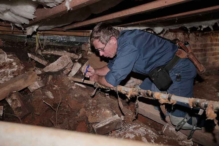 Rick Eades climbs under the foundation of city reporter Tim Summers Jr.'s rental home to check the conditions of the pipes. Photo by Imani Khayyam.