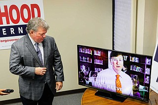 """Mississippi Attorney General Jim Hood, the Democratic nominee for governor, watches while an aid plays an education ad from Republican opponent Tate Reeves that Hood calls """"fraudulent."""" Photo by Ashton Pittman."""