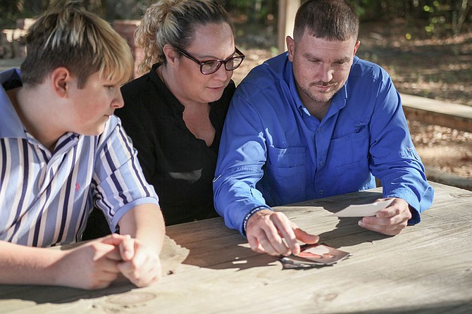 Dusty Houser (right) leafs through photographs of his father Paul Houser alongside his son Kyler and wife Ree. Paul Houser is serving a 60-year prison for a drug-related offense because of Mississippi's habitual-offender laws. Photo courtesy FWD