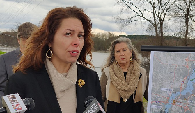 """The Rankin Hinds Pearl River Flood & Drainage Control District, called the Levee Board, is confident that the """"One Lake"""" project will address flood control in Jackson. But environmentalists, including Jill Mastrototaro, left, policy director for Audubon Mississippi, gathered in front of the Pearl with a presentation challenging their certainty. Mayor of Monticello, Miss., Martha Watts, right, joined them, sharing her fears of downstream effects on local industry. Photo by Nick Judin"""