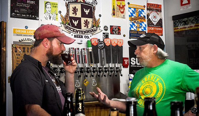 Chris Edwards (left), proprietor of Bicentennial Brewery, sips a craft beer while listening to Larry Voss (right), the owner of LD's BeerRun. Photo courtesy Caleb McCluskey