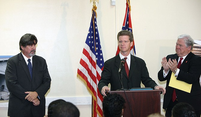 U.S. Housing and Urban Development Secretary Shaun Donovan (center), Gov. Haley Barbour (right) and Mississippi Center for Justice Housing Director Reilly Morse in North Gulfport in 2010 to announce a $132 million settlement of the Mississippi Center for Justice's lawsuit against HUD over diversion of housing funds to expand the State Port at Gulfport. Photo courtesy of Mississippi Center for Justice