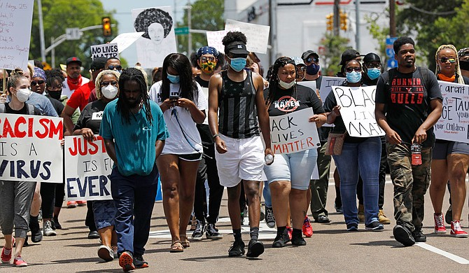 Protesters marched in Mississippi's capital city on Monday, with some stopping to lie on the ground outside Jackson's main police station to remember George Floyd, a black man who died after a Minneapolis police officer pressed his knee into Floyd's neck for several minutes. Photo by Rogelio V. Solis via AP
