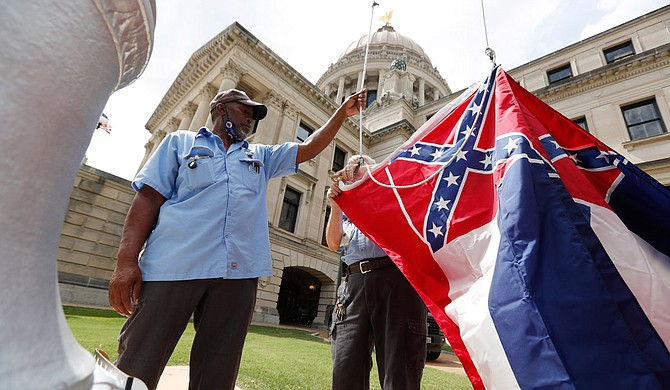 Mississippi Department of Finance and Administration employees Willie Townsend, left, and Joe Brown, attach a Mississippi state flag to the harness before raising it over the Capitol grounds in Jackson, Miss., Tuesday, June 30, 2020. The two men raised about 100 flags, provided by the Secretary of State's office, for people or organizations that purchased a state flag that flew over the grounds. Gov. Tate Reeves will sign a bill Tuesday evening retiring the last state flag with the Confederate battle emblem during a ceremony at the Governor's Mansion. Upon the governor signing the bill, the flag will lose its official status. Photo courtesy Rogelio V. Solis via AP
