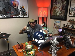 """Co-owner, illustrator, designer and overall """"creator of cool stuff"""" Jesse Labbé sits at his desk in his office, surrounded by artwork, equipment and various geek-related memorabilia. Photo by Nate Schumann."""