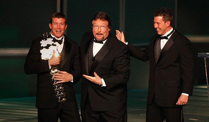 "In this March 27, 2010, file photo, WWE Superstar Ted DiBiase Jr. (left), with brother Brett DiBiase (right), induct their father ""Million Dollar Man"" Ted DiBiase (center) into the 2010 WWE Hall of Fame at the Ceremony in Phoenix, Ariz. Photo courtesy Rick Scuteri/WWE via AP"