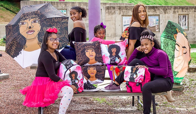 Besides custom cards, Designs by Dij creates products such as pillows, umbrellas, tote bags and more—as (from left) Madisyn Lush, Micah Lush, Harmonie Lush, Vanise Lush and Mckaylynn Lush model here. Photo courtesy Khadijah Muhammad